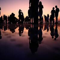 Silhouettes of people standing on a mirrored surface during golden hour | Mario Purisic / Unsplash