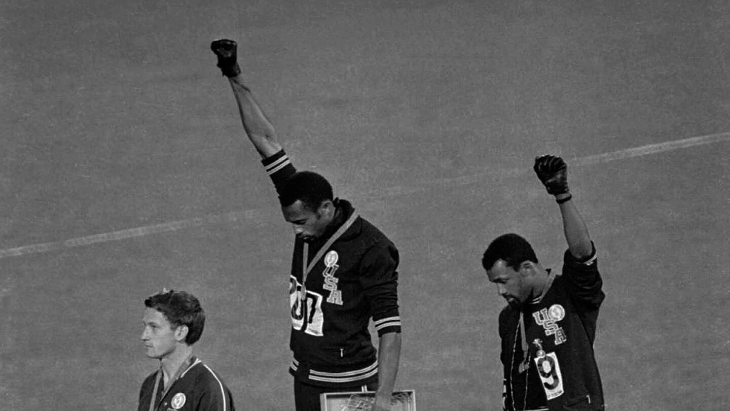 "Track and field athletes Tommie Smith and John Carlos raise their fists at the medal podium in a Black Power salute at the 1968 Summer Olympics. | ""The Stand"""