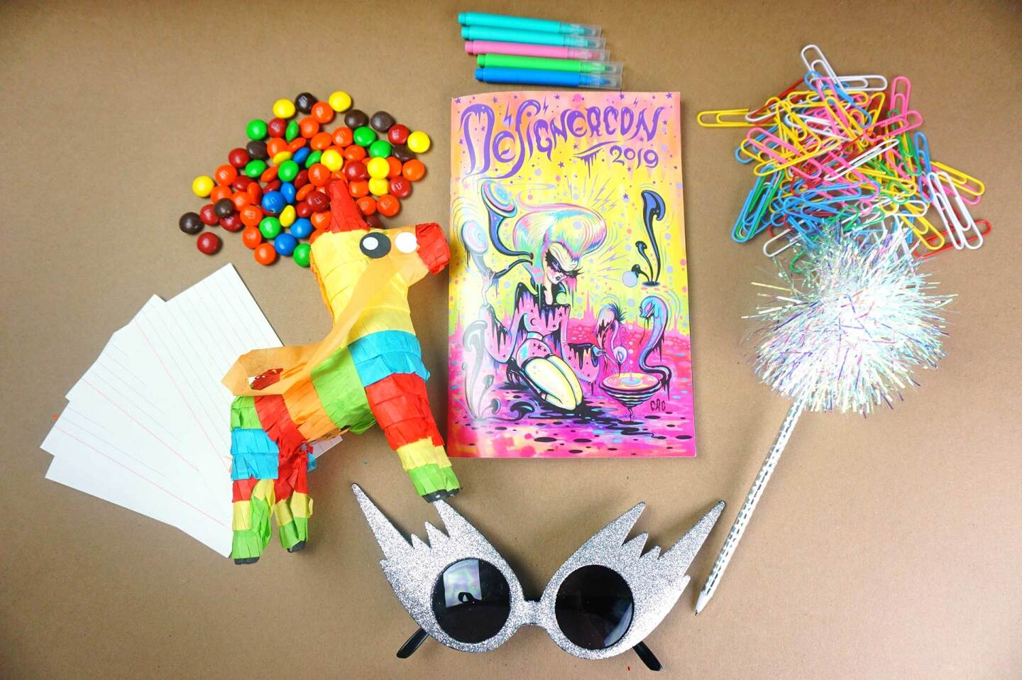 Index cards, spiky sunglasses, a book, a small piñata, markers and colorful paper clips are laid out on a table.