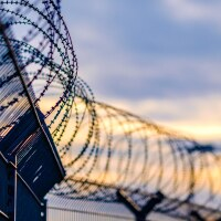 A fence with barbed wire. | iStock via Getty Images