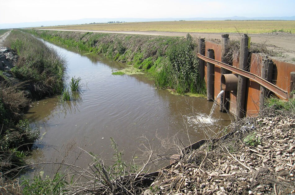 Drainage Canal with Water Pouring from Metal Pipe