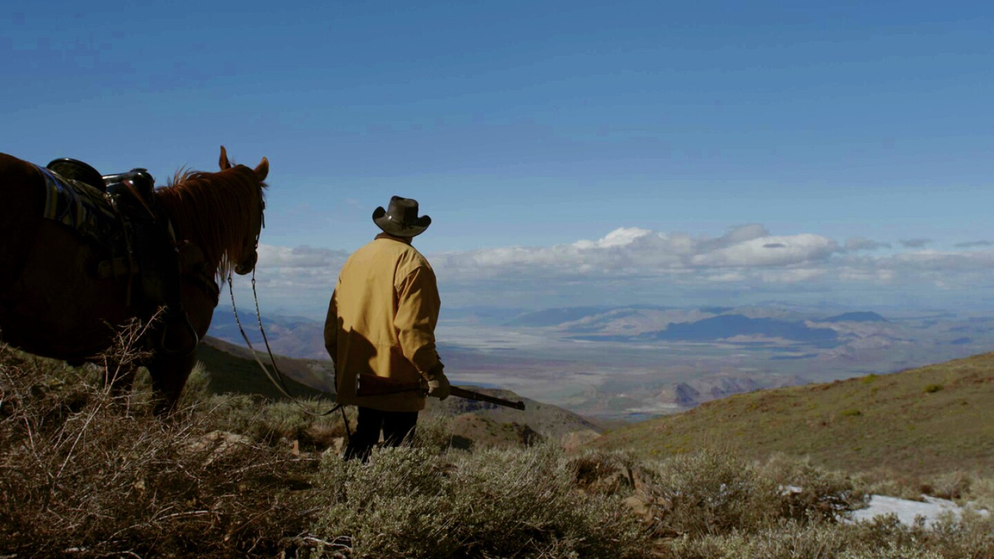 A man wearing a hat stands next to his horse and looks out into the wilderness of Nevada.