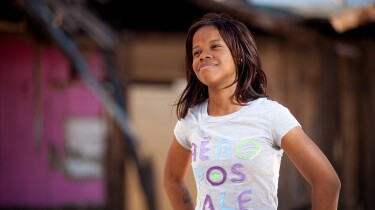 A young girl poses as she looks on with a content smile.