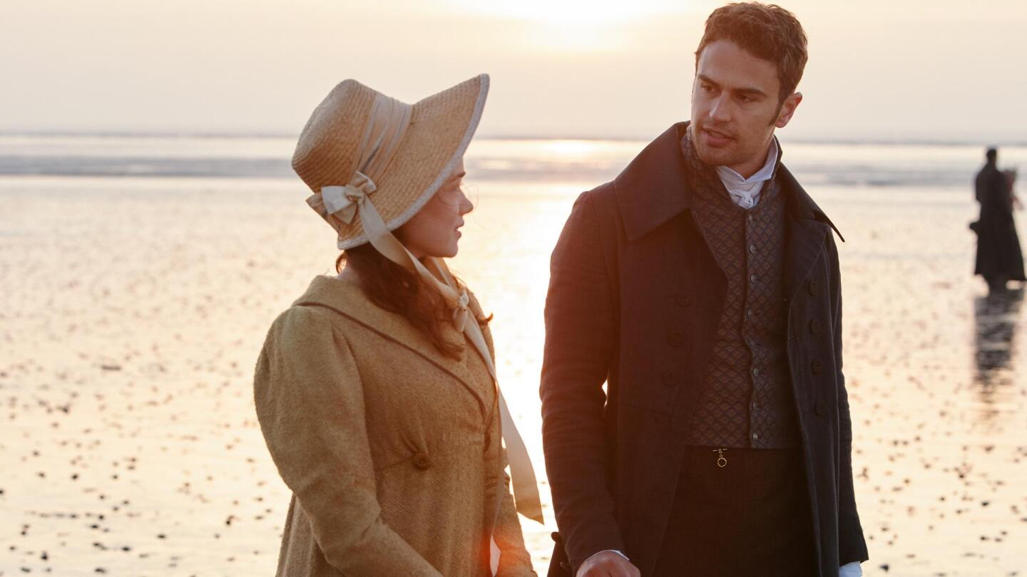 """A man faces a woman at his side on a beach. 