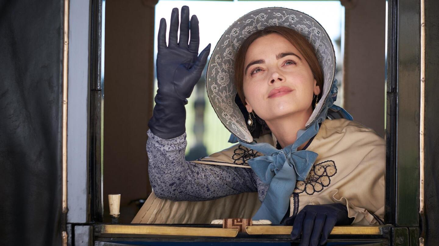 """Queen Victoria (Jenna Coleman) waves from a carriage window. 