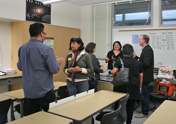 Classroom teacher, Leticia Ortiz talks to Kevin, Alisa and Cecilia about the student's projects as Damian and Ruth share a conversation.
