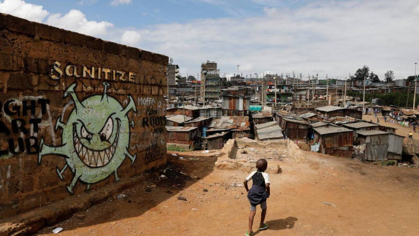 A boy walks in front of a graffiti promoting the fight against the coronavirus disease (COVID-19) in the Mathare slums of Nairobi, Kenya, May 22, 2020. | REUTERS/Baz Ratner