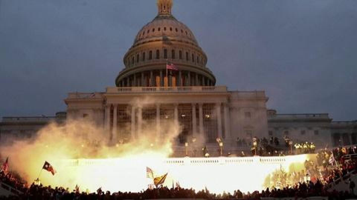 Fire erupts amidst a mob outside the U.S. Capitol.