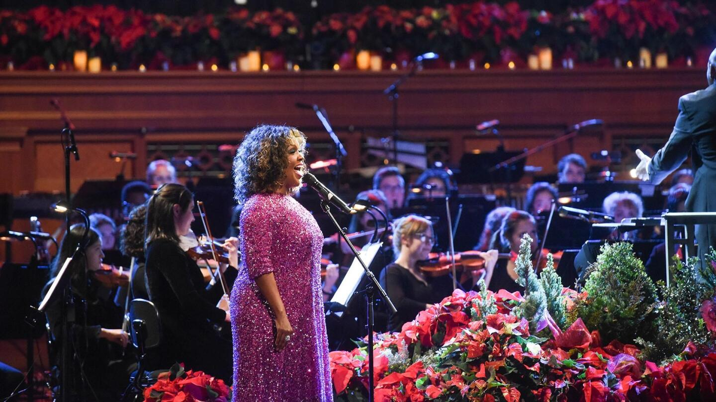 A singer performs on stage with an orchestra beside her.