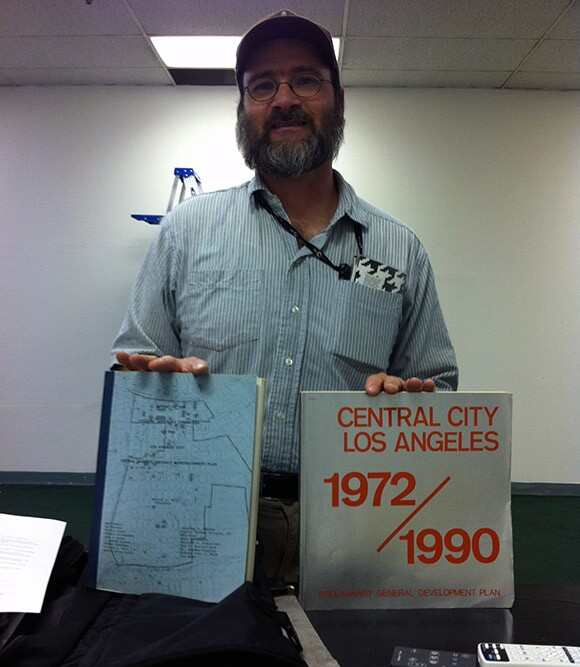 Michael Holland with Blue and Silver Book | Courtesy Los Angeles Poverty Department
