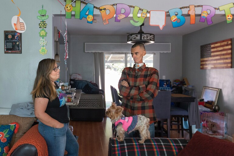 """Rocio and Brian stand in the living room of their home. The walls are painted in a powder blue color. To the right, there is an American flag wall art. Above them hangs a """"Happy Birthday"""" banner."""