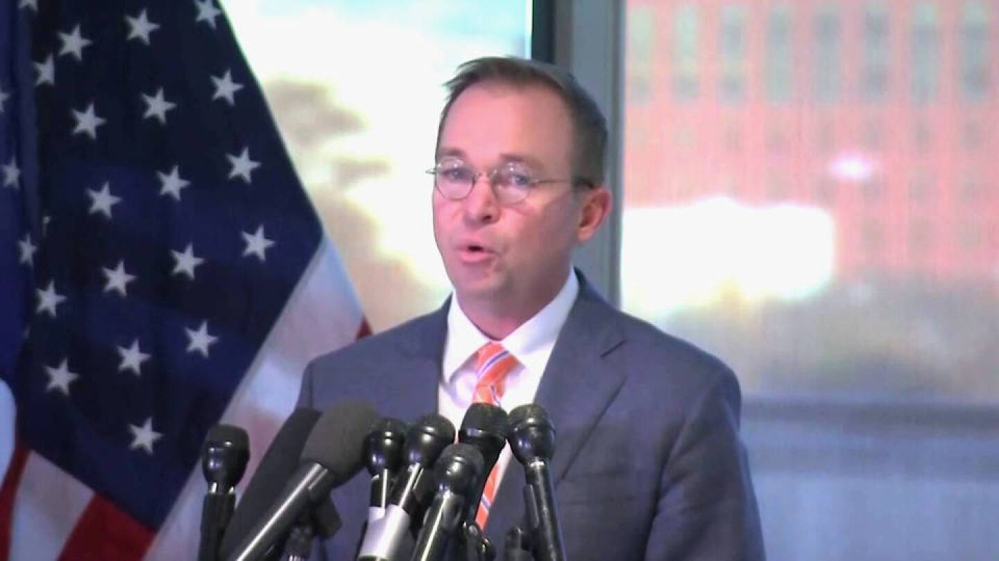 Mick Mulvaney, director of the Office of Management and Budget, speaking at a podium. | Democracy Now