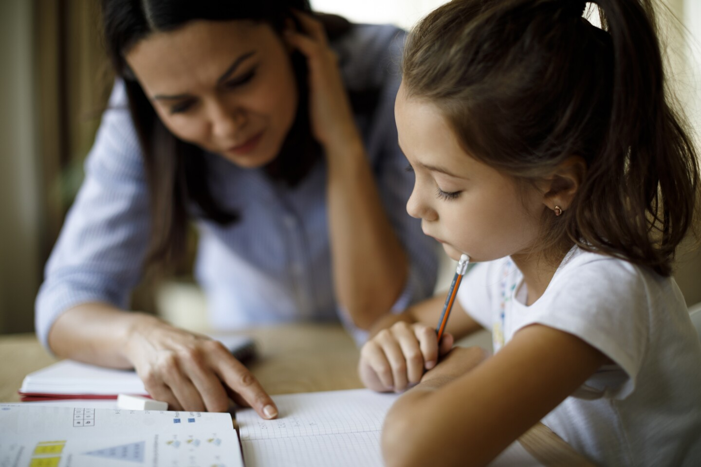 Young student being tutored by an adult. | iStock