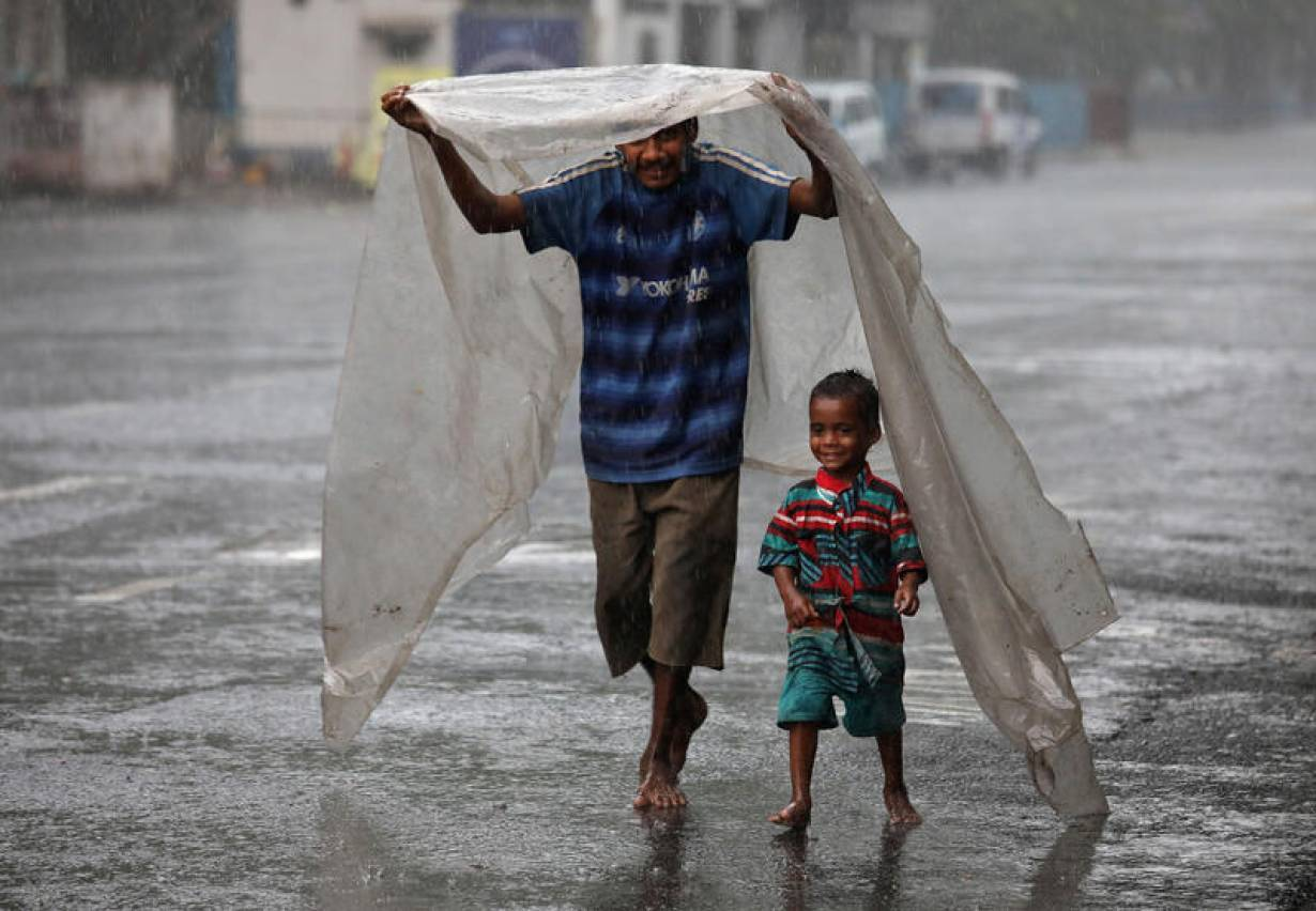 A homeless man and his son cover themselves with a plastic sheet to protect themselves from rain as they walk to a shelter, during a nationwide lockdown to slow the spreading of the coronavirus disease (COVID-19), in Kolkata, India, April 27, 2020. REUTER