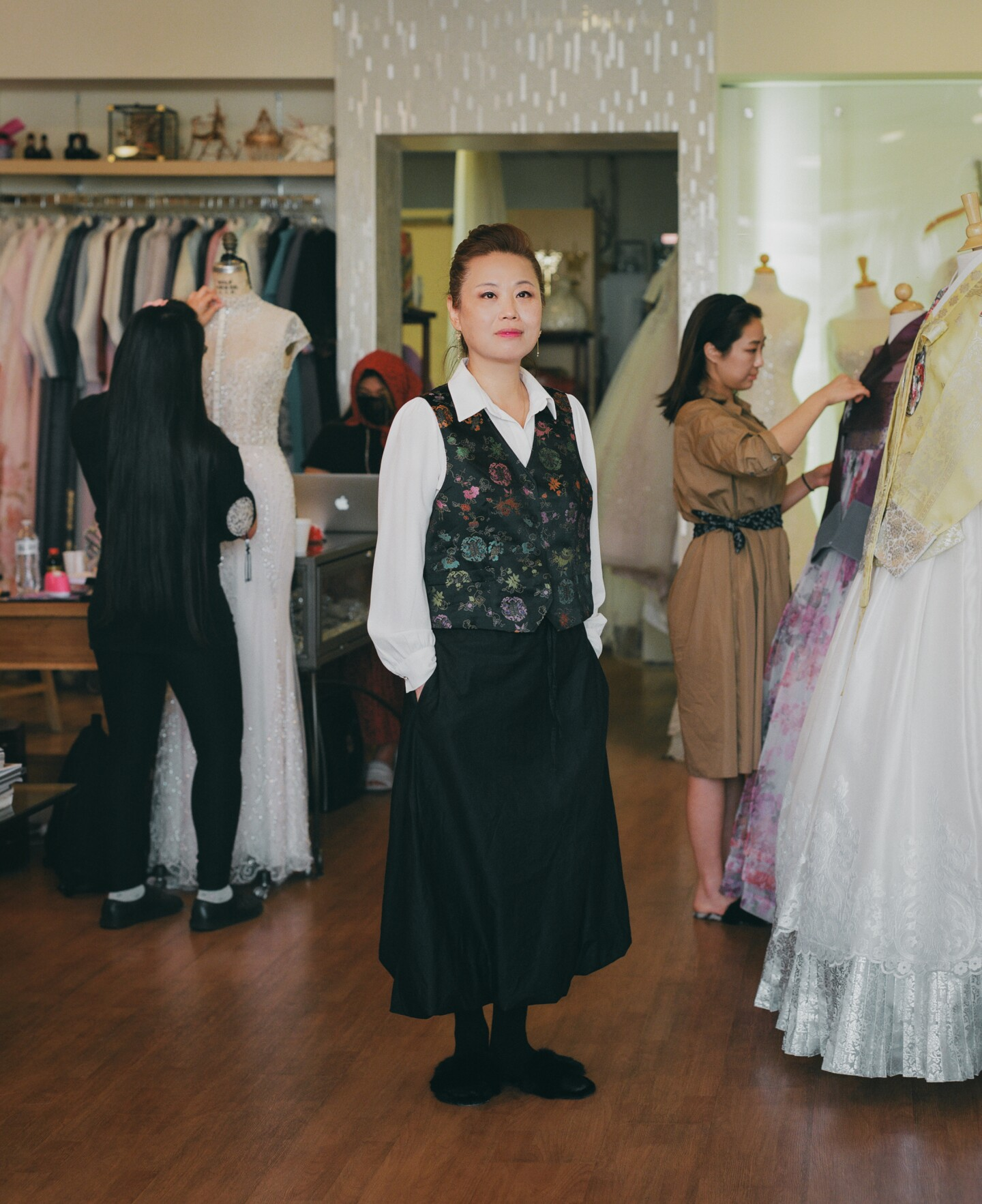 Laura, a hanbok maker, stands in her shop with dresses and tailors.