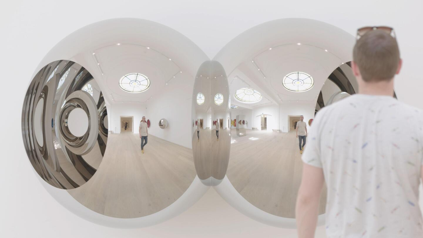 A man sees his reflection in an art installation.