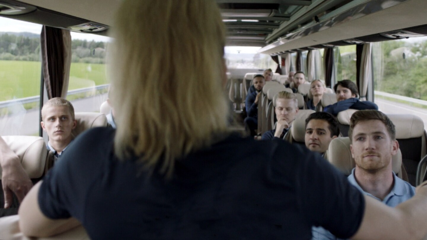 "Helena speaks in front of a bus full of people. | From ""Home Ground: No Comment."""