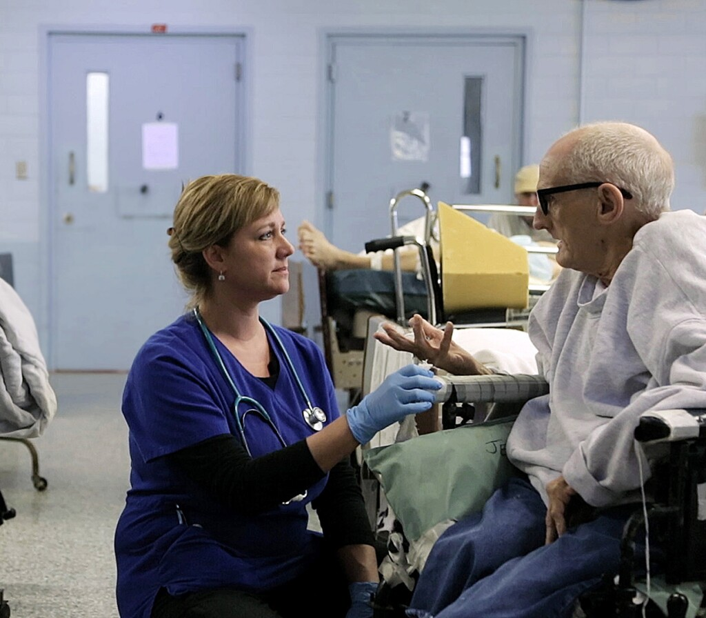 "Nurse Tonia kneels to a patient in a wheelchair. | Still from ""American Nurse"" for ""Link Voices"""