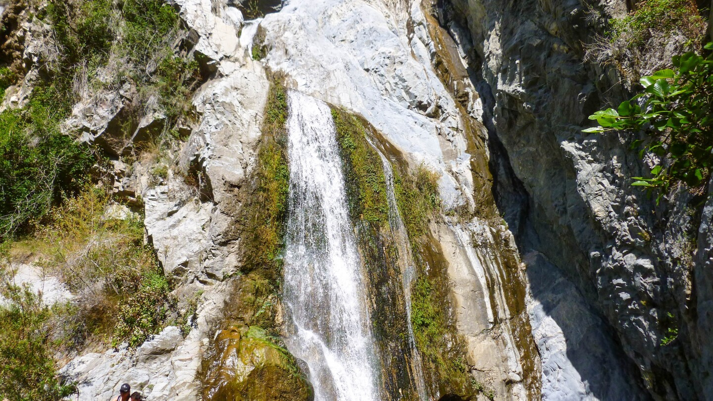 The waterfall at Fish Creek in the Angeles National Forest.  To the bottom left corner are two hikers resting by the creek.