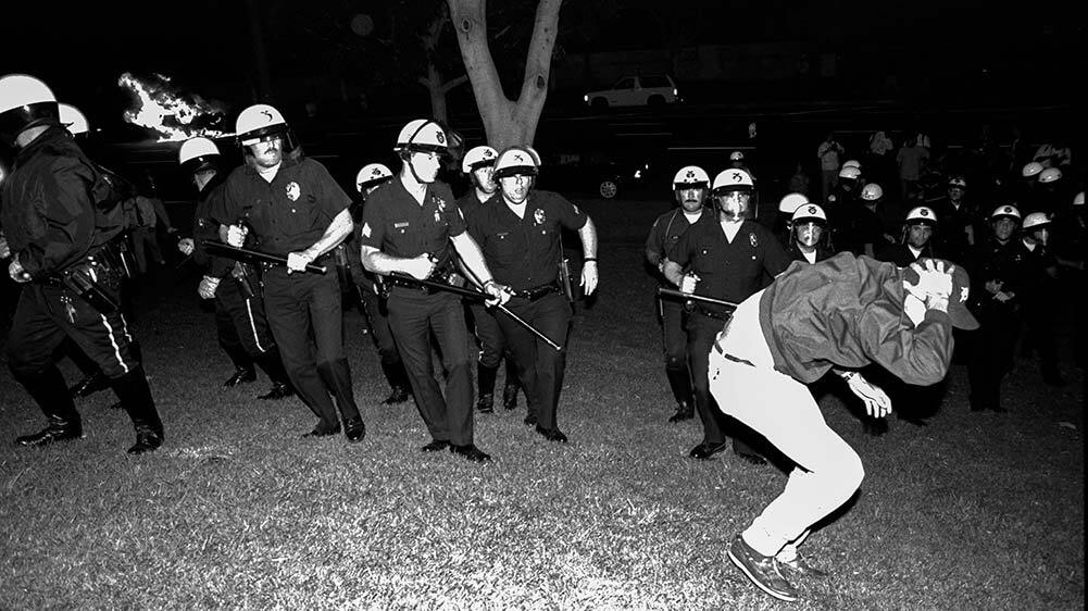 Los Angeles, 1992: Scan from negative of LAPD officers from Parker Center advance across City Hall lawn against stricken rioter in the early evening. | Andy Katz/Corbis via Getty Images