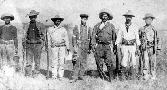Julio Rodriguez (at center, holding camera) in Mexico with revolutionary fighters, circa 1910. | Courtesy of the Los Angeles Public Library
