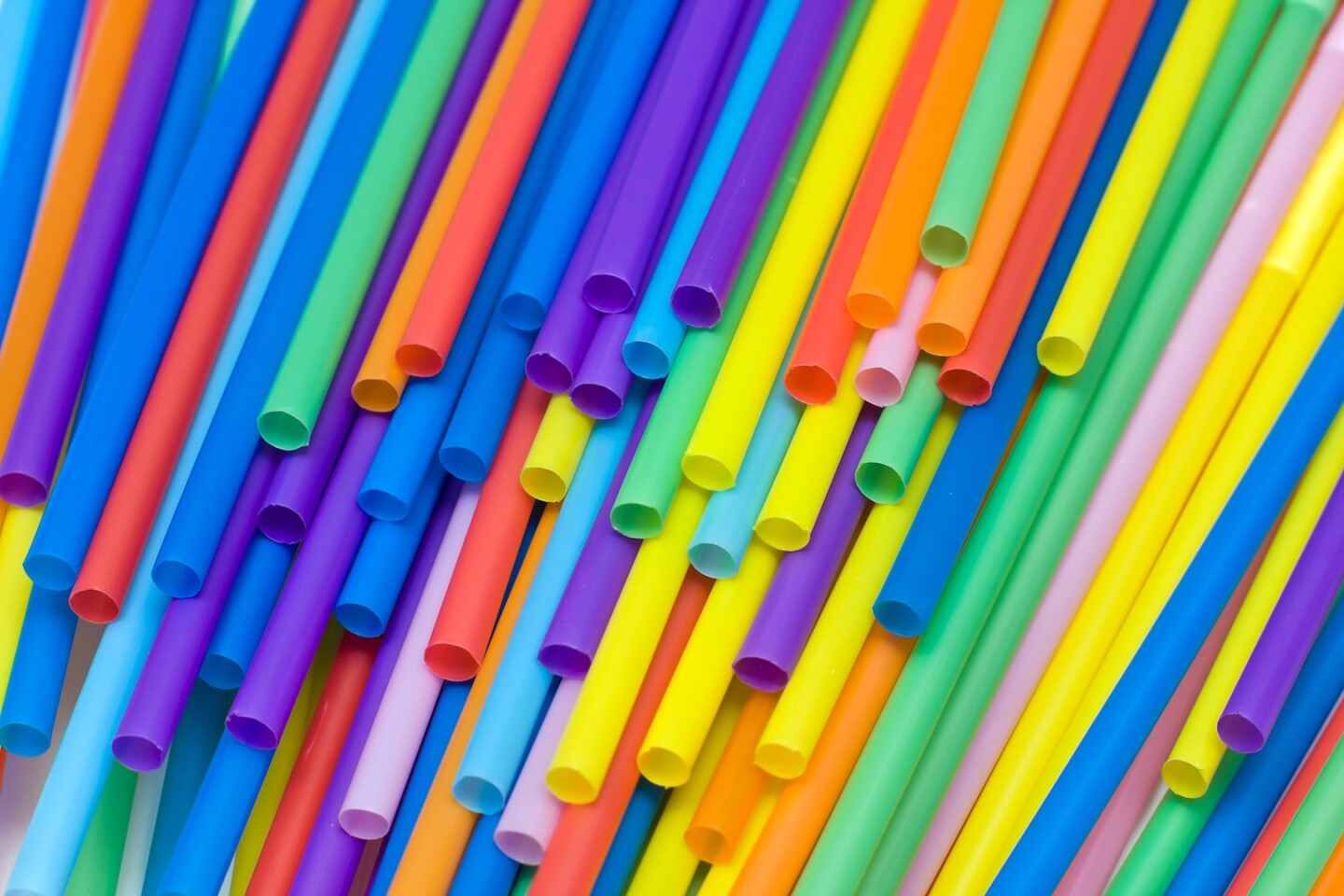 Multi-colored plastic straws thrown on top of each other