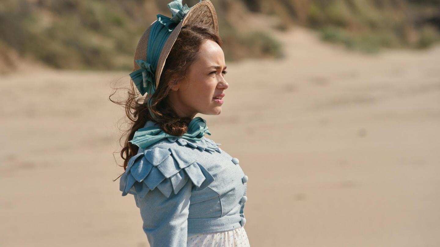 """A woman squints while standing in the sand. 
