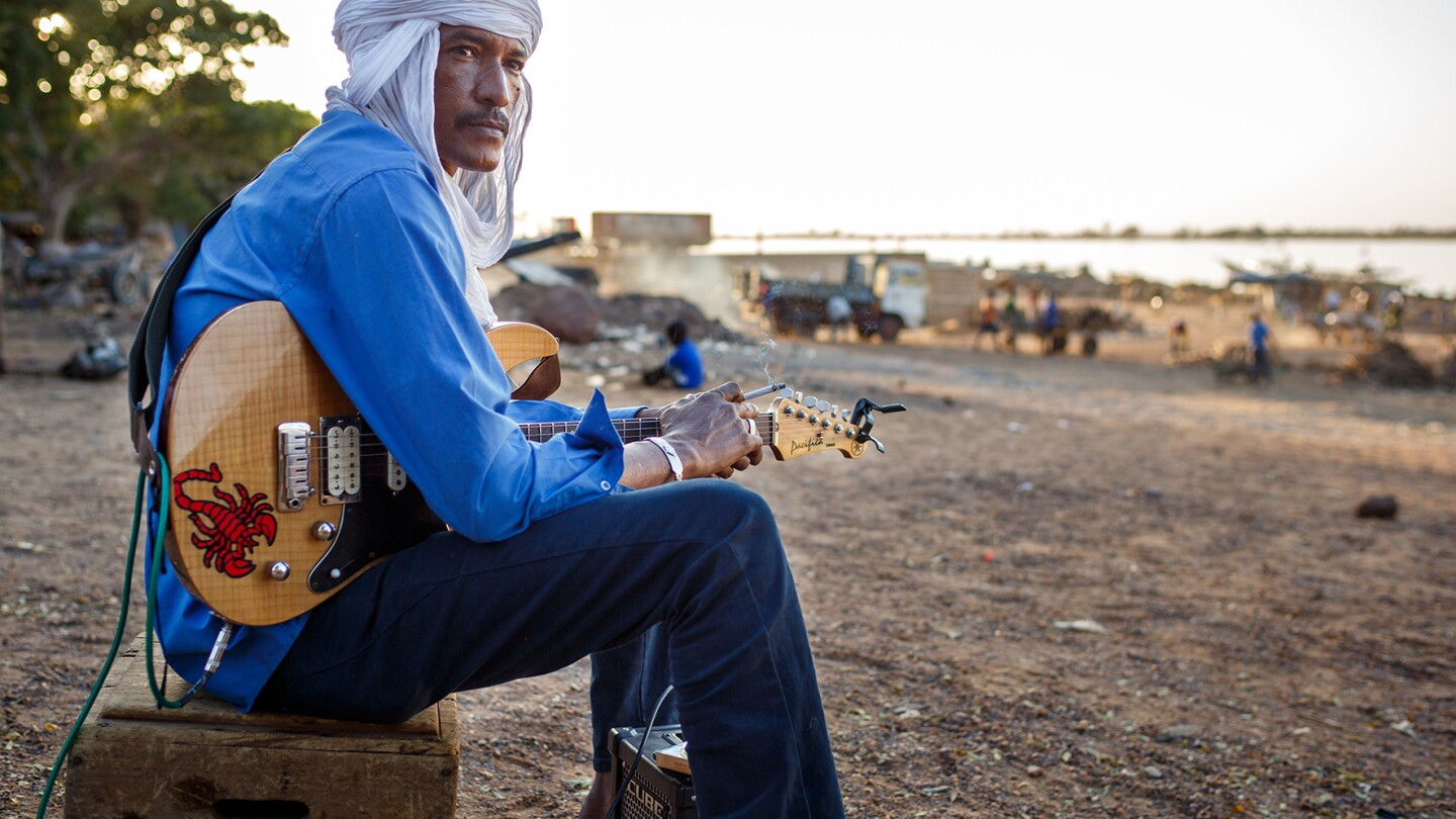 """Ahmed Ag Kaedi and his band Amanar play the famous song """"Desert Blues,"""" a modern version of traditional Tuareg music. Currently the musicians live in exile, expelled by the Islamist from their homes in the desert.   © Konrad Waldmann, 2016"""