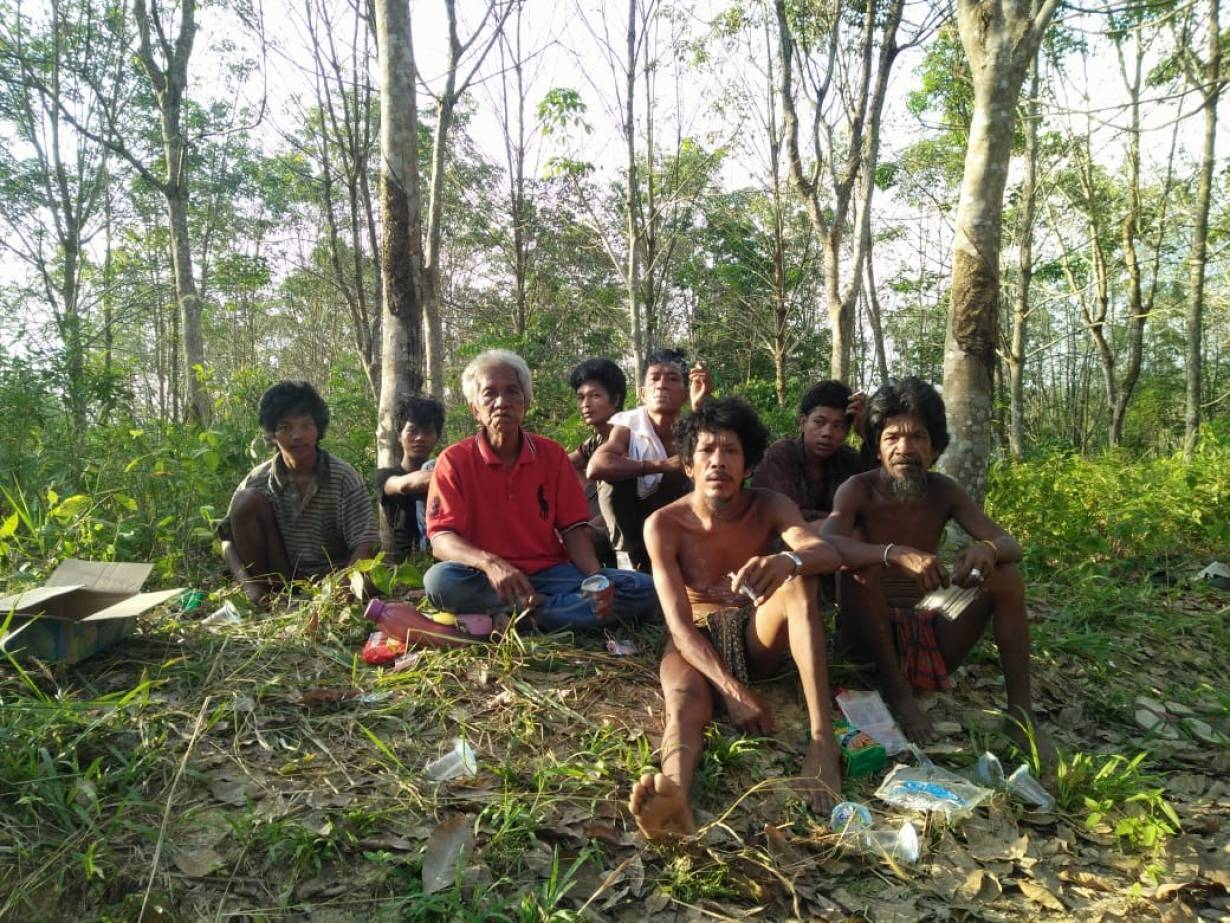 Orang Rimba elder Tumenggung Nyenong, 57, (third from left in red shirt) is pictured in the forest of Bukit Duabelas national park with other tribe members, Sumatra, Indonesia, in June 2020. | Anggun Nova/Handout via Thomson Reuters Foundation