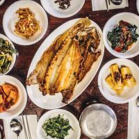 An overhead shot of banchan, Korean side dishes, laid out on a table.