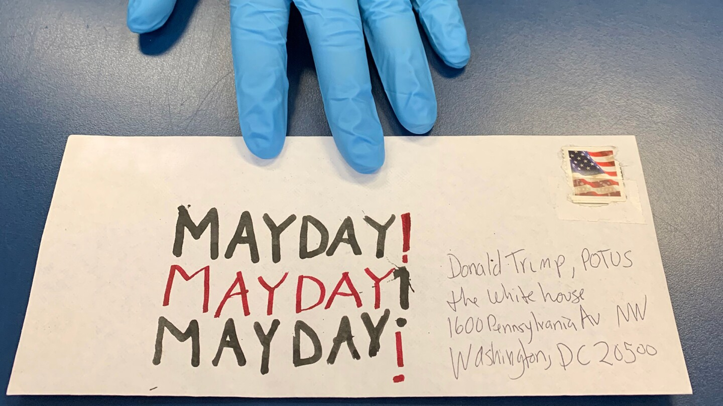 "A gloved hand holds an envelope in Sean Griffith's contribution to Susan Silton's ""Mayday! Mayday! Mayday!"" project 