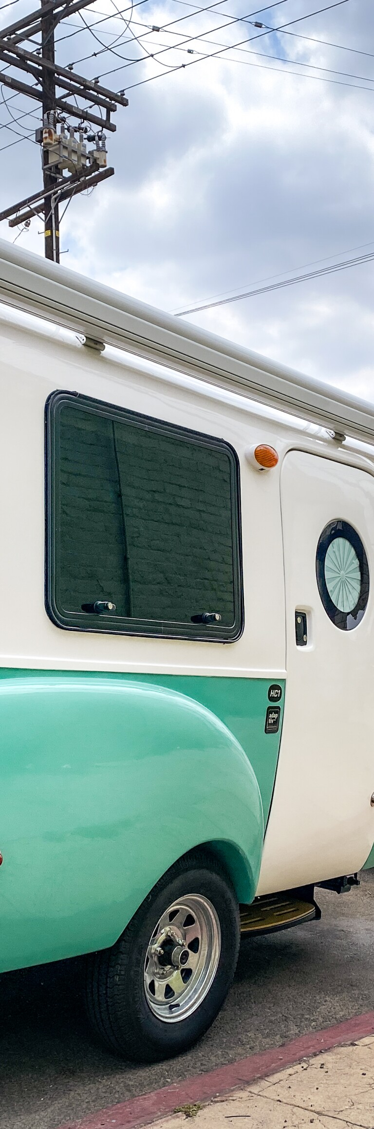 Pichardo's Mobile Art Lab, a teal and white trailer, is parked on the side of the road.