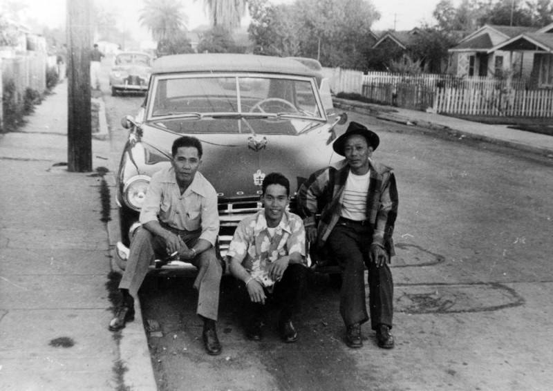 Black and white photo of three men posing in front of a car