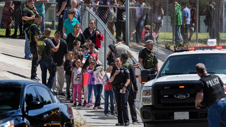 San Bernardino Police officers help evacuate children to awaiting school buses after a shooting inside North Park Elementary School.