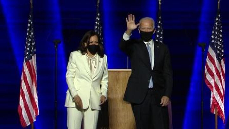 Joe Biden and Kamala Harris wearing masks as Biden waves to the audience.