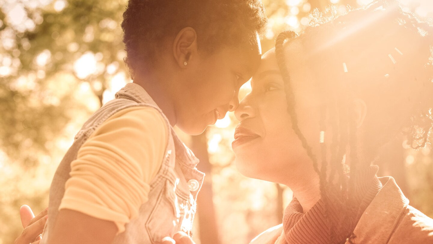 A mom looks into a small child's eyes as they are both enveloped in warm light