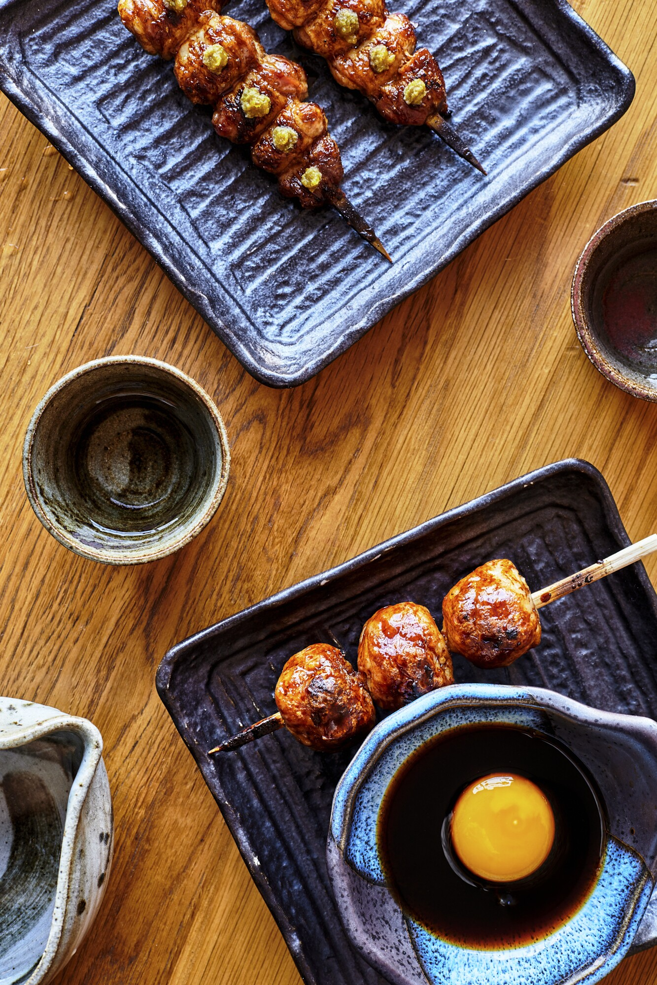 A cup of junmai sake is found set beside charcoal-grilled chicken meatballs and chicken oysters.