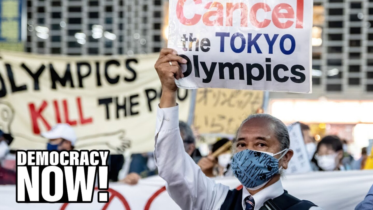 """A man wearing a face mask holds up a sign that reads, """"Cancel the Tokyo Olympics."""""""