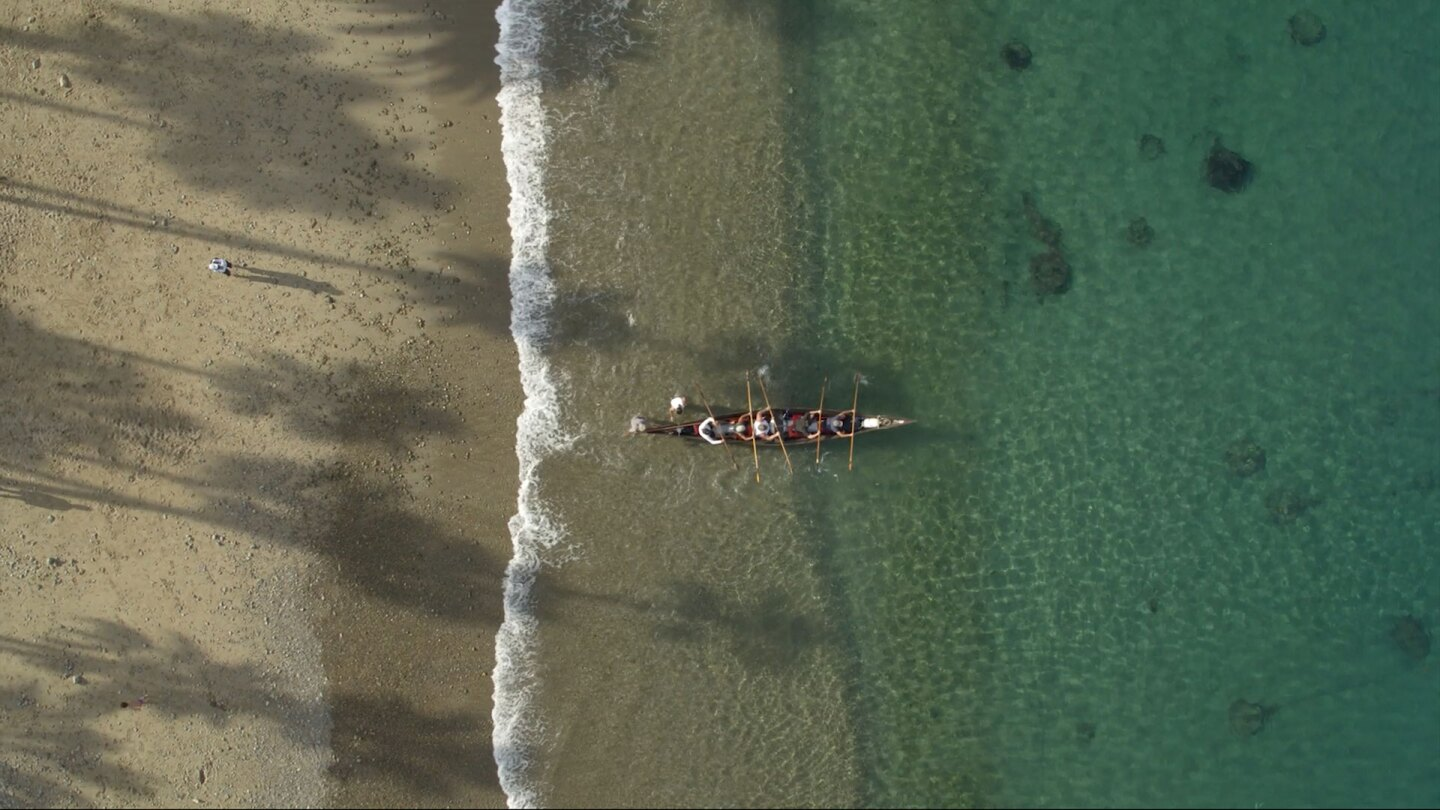 "Aerial view of a traditional Tongva canoe launching into the ocean. | Still from ""Tending Nature"""