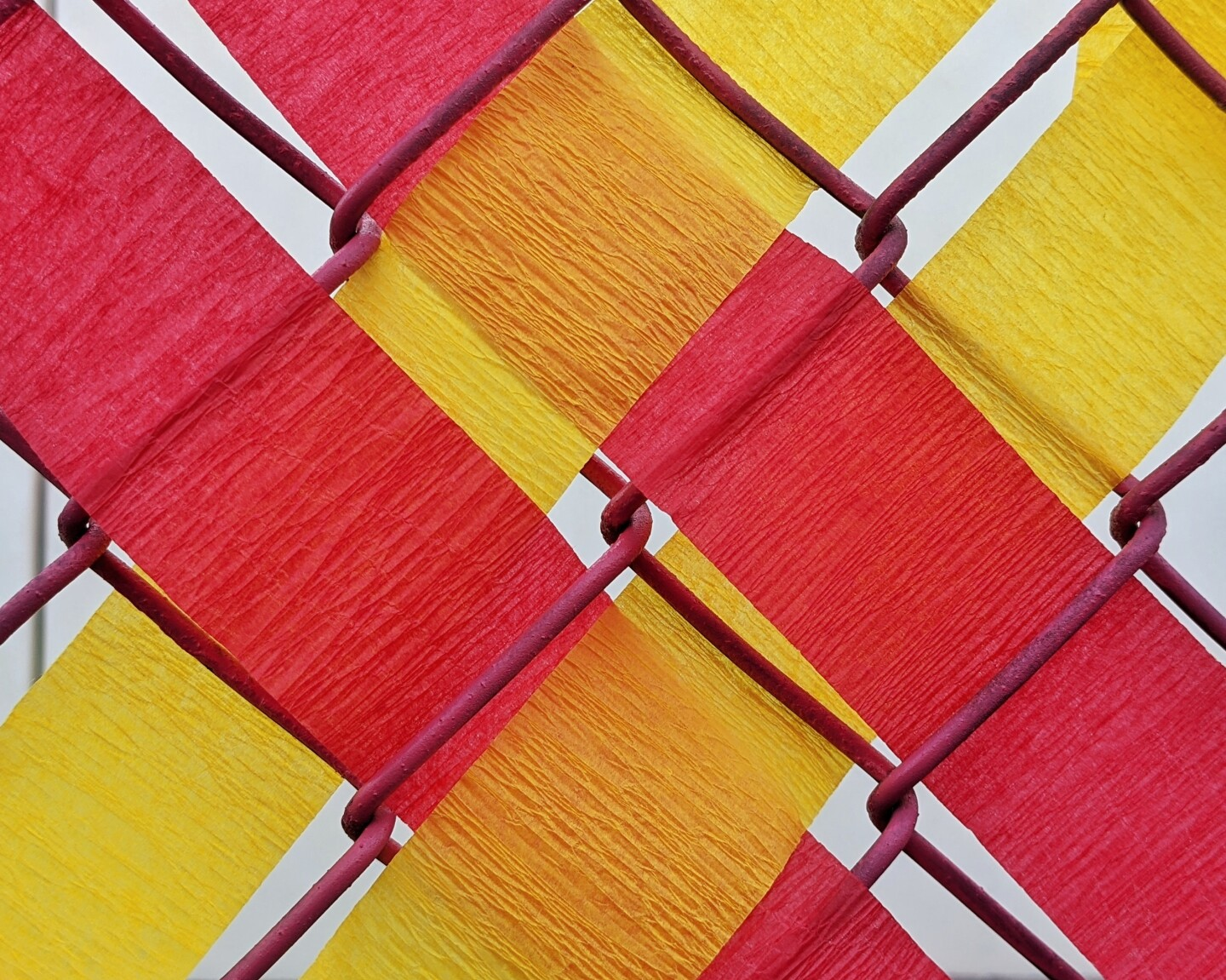 Pieces of red and yellow paper are woven in a pattern on a fence.