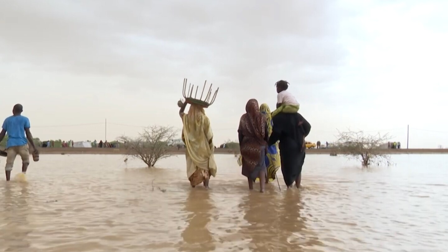 A group of people wade through flood water.