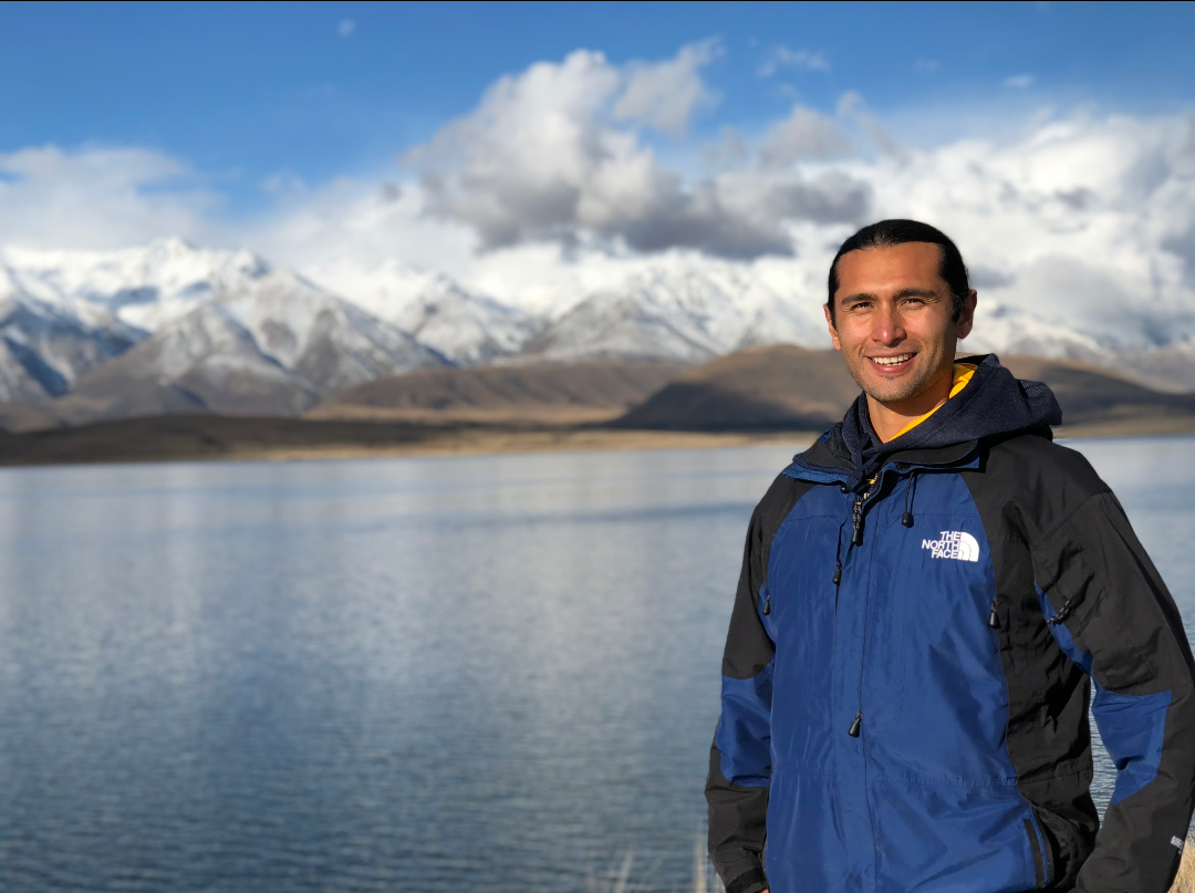 A man in a blue jacket smiles in front of a lake.
