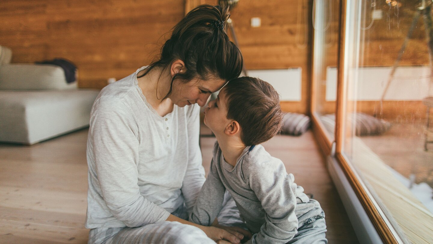 A parent and child wearing pajamas hold their heads close to each other. istock