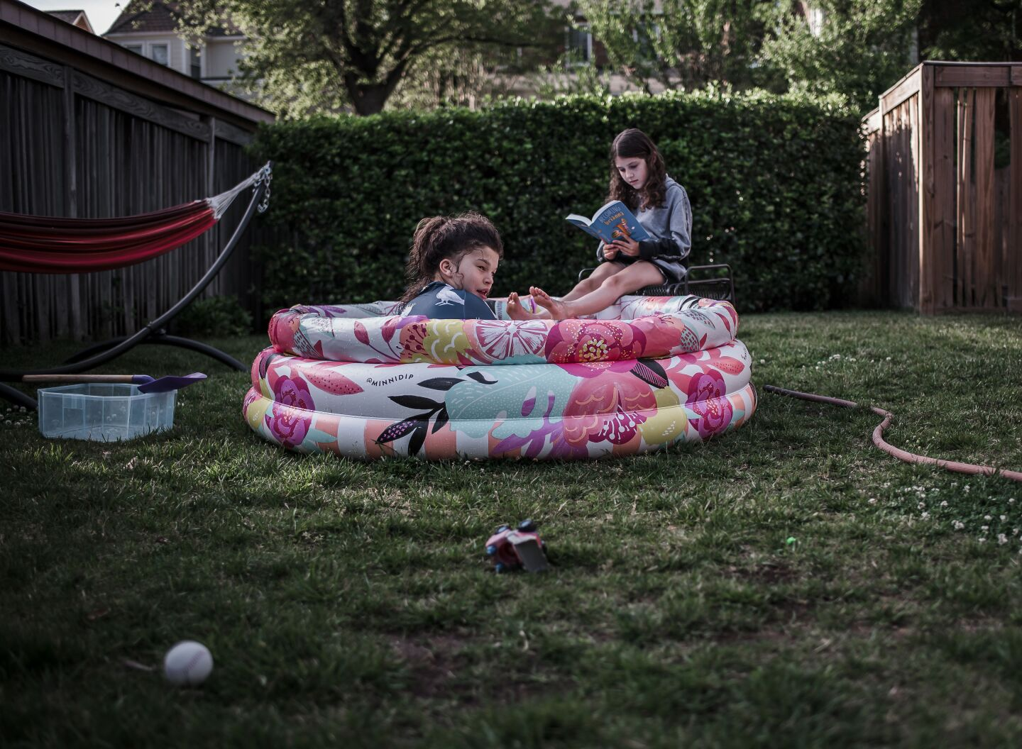 Two young girls playing in a small inflatable pool in the garden