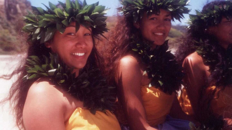 Hula dancers smile into the camera.