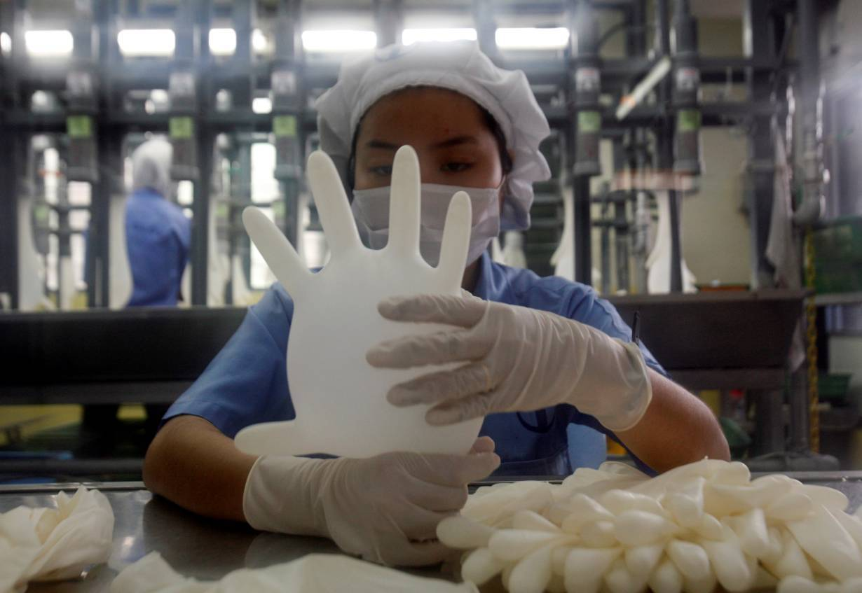 "49-xxtxt left""> 							<p>FILE PHOTO: A worker carries out a test on a glove at a Top Glove factory outside Kuala Lumpur June 25, 2009. 