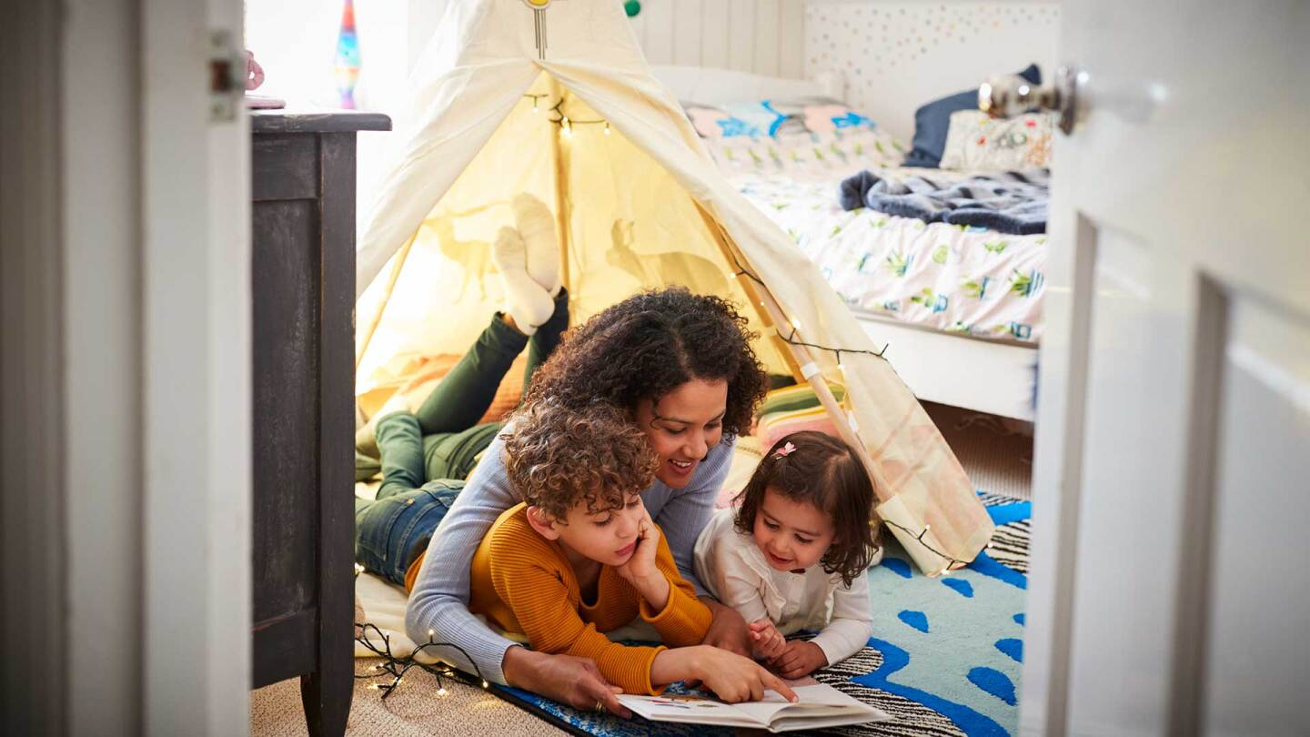 A mother and children read in an indoor tent.