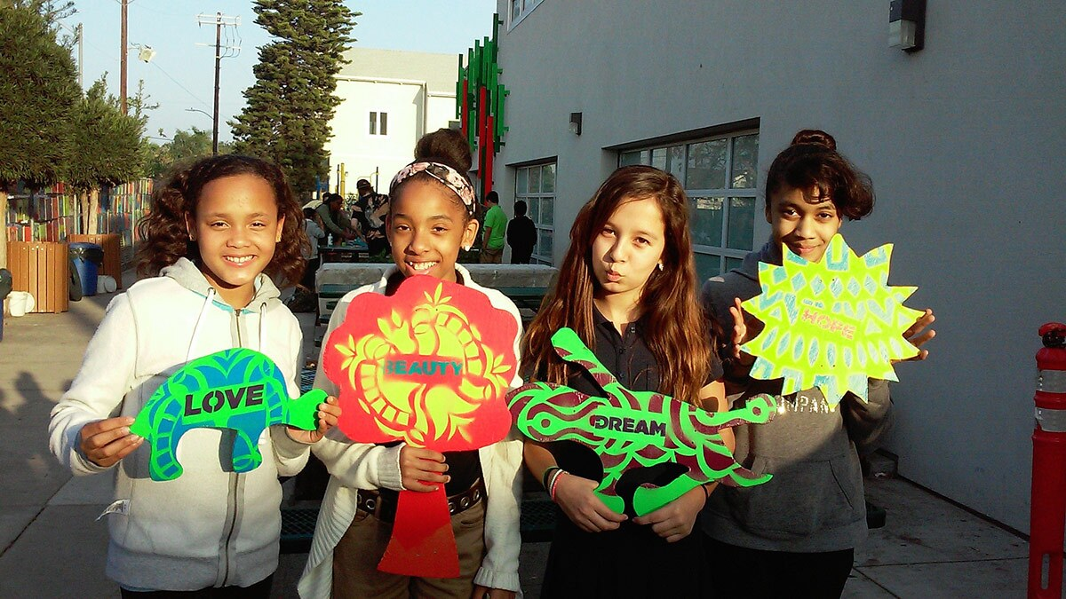 Three young girls pose with their contributions to an installation designed around the question: what sustains a community?