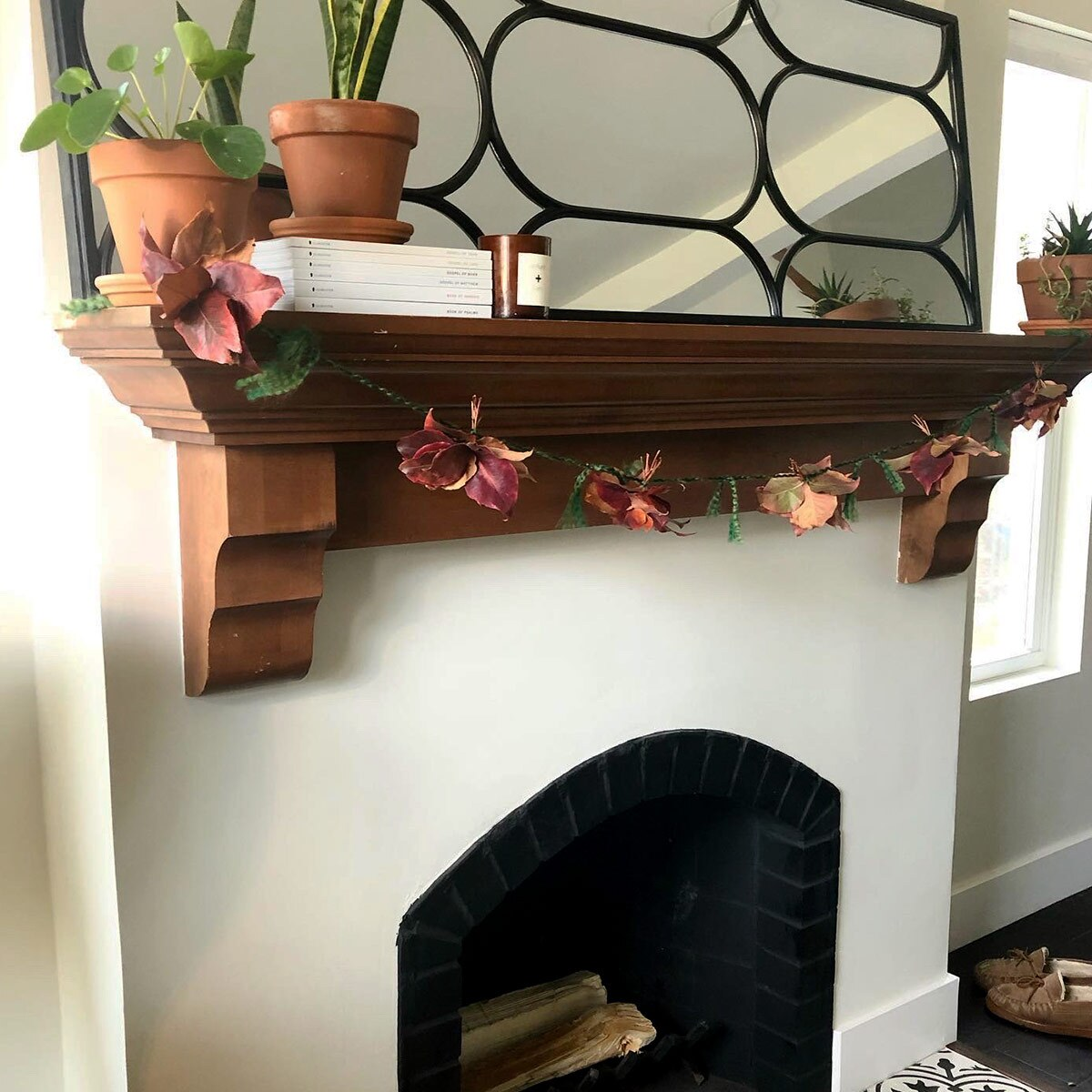 A garland made of fall leaves hangs on top of a fireplace.