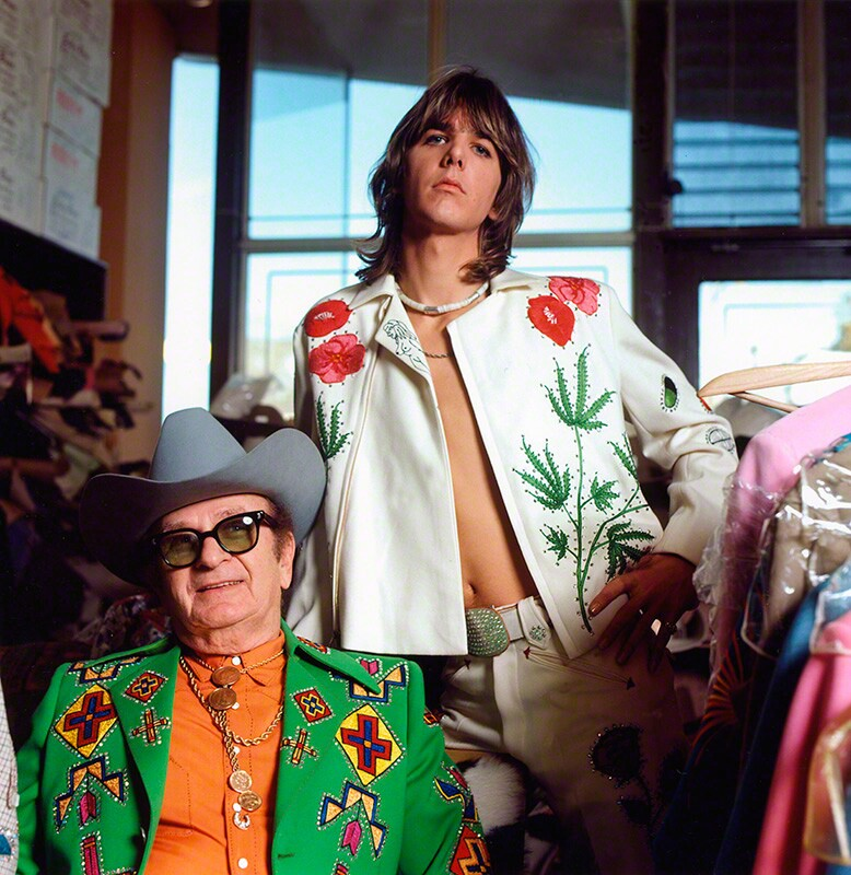 Gram Parsons (standing), adopting the rhinestone look of his country music heroes, in a personalized suit designed by Nashville's favorite tailor, Nudie Cohn (seated), at Nudie's Rodeo Tailors shop, Los Angeles, 1968 © Raeanne Rubenstein